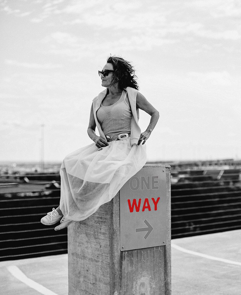 Woman sitting on top of one way sign