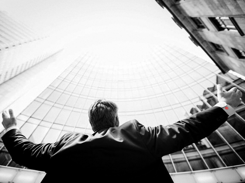 Business Man in Front of Building with Arms Open