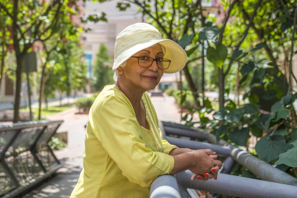 Women of and older 50 can start fashion trends. The woman depicted here is wearing a sunhat and a quarter length sleeve shirt, softly smiling.
