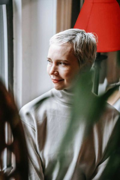 This younger woman has dyed her hair white and she's wearing a turtle neck shirt, looking out of a window.