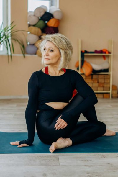 This older woman is wearing athletic leggings and a cut off long sleeve shirt while stretching on a yoga mat.