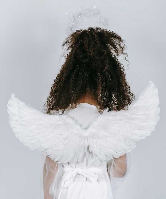 This girl has her back turned from the camera while she's wearing angel wings and a white dress. Girls are told at a young age to be good little angels.